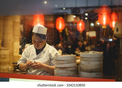 London, UK - March, 2018. A female cook preparing dumplings in a restaurant in China Town in Soho. China Town was established in 1880th by Chinese sailors and traders.