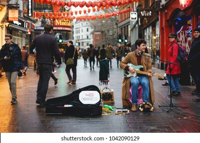London, UK - March, 2018. Street musician playing a guitar during a performance in Chinatown.
