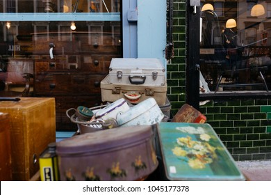LONDON, UK - MARCH 21, 2016: Stack of vintage suitcases and various vintage items in Chatsworth Road Market. The market has a long heritage and is located on one of London's longest high streets.