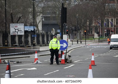 London, UK, March 22, 2017 An armed police officer stands guard near Westminster Bridge and the Houses of Parliament London. After the terrorist attack