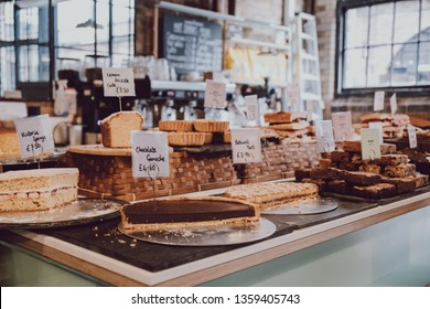 London, UK - March 23, 2019: Cakes and desserts with price tags on sale inside Camden Grocer, a luxury deli and cafe in Camden's Stables Market, London, UK.