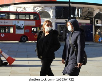 London / UK - March 23rd 2020: People in face masks walk around London's popular tourist destination Piccadilly Circus as people are told to  self isolate during the COVID-19 coronavirus