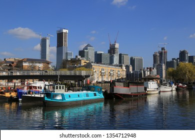London / UK - March 24th 2019: Boats in Greenland Quay Canada Water Surrey Quays with Canary Wharf In the background on a sunny spring day