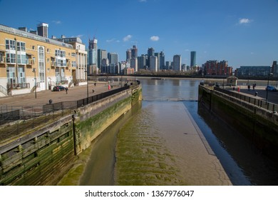 London / UK - March 24th 2019: Canary Wharf in the background, the lock at Greenland Quay in the foreground. Surrey Quays, docks marina, London