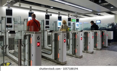London, UK - March 26, 2018: Air travellers pass through automated passport border control gates at Heathrow Airport.