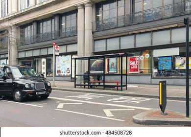 LONDON, UK - March 26: Whiteleys shopping center bus stop with people sitting on the bench while waiting  in London, UK - March 26, 2016; Public bus stop in London urban street with black cab on side.