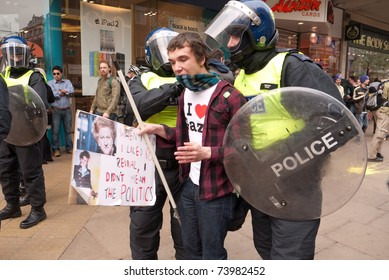LONDON, UK- MARCH 26:Two riot police officers talk to a protester on Oxford Street, during the day of protests over Government cuts in central London.March 26, 2011 in London, UK.
