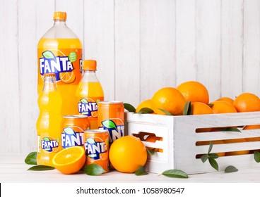LONDON, UK - MARCH 31, 2018: Plastic bottles and aluminium tins  of Fanta orange soft drink on white wooden background with box of raw oranges.