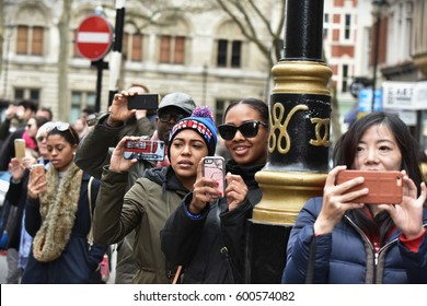 London, UK - March 4, 2017: Bystanders take photos as protesters march during a demonstration in support of the NHS. Thousands marched against NHS spending cuts, hospital closures and privatisation.