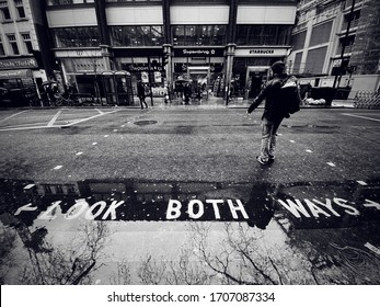 LONDON, UK - MARCH 4 2020: Man crosses a road with a Look Both Ways street sign towards shops