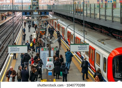 London, UK - March 5th, 2018: Commuters at platform of London Underground Earl's Court Station in West London. The station services the District, Circle and Piccadilly Lines