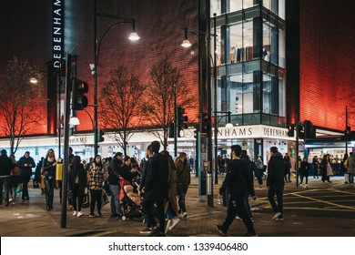 London, UK - March 9, 2019: People walking in front Debenhams store on Oxford Street, London, in the evening. Oxford street is one of the most famous shopping streets in London.