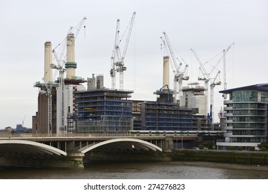 LONDON, UK - MAY 01: Battersea power station surrounded by cranes and scaffoldings. May 01, 2015 in London. The chimneys of the emblematic structure are being rebuilt as part of its redevelopment.