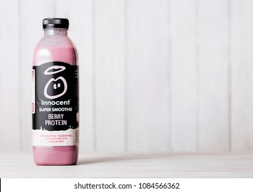 LONDON, UK - MAY 03, 2018: Bottle of Innocent berries smoothie fruit drink with vitamins on wooden background with fresh berries.