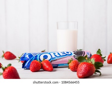 LONDON, UK - MAY 03, 2018: Oreo strawberry original cookies with fresh berries and glass of milk on wooden background.