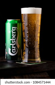 LONDON, UK - MAY 03, 2018: Cold glass and aluminium can of Carlsberg beer on wooden background. Danish brewing company founded in 1847.