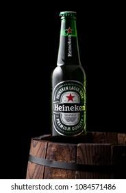 LONDON, UK - MAY 03, 2018: Bottle of Heineken Lager Beer on top of wooden barrel and black background. Heineken is the flagship product of Heineken International