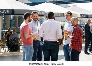 London, UK - May 10, 2017 - Group of young men drinking at a dockside bar in Canary Wharf
