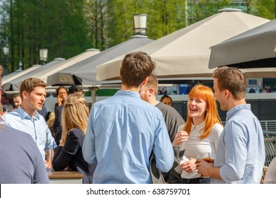 London, UK - May 10, 2017 - A young businesswoman drinking with her colleagues at a packed outdoor bar in Canary Wharf on a sunny day