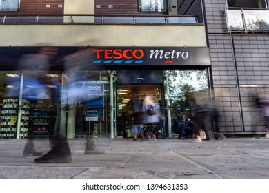 London, UK - May 10, 2019. A man begs at the entrance to a Tesco Metro chain supermarket as shoppers walk by in the middle-class borough of Islington.