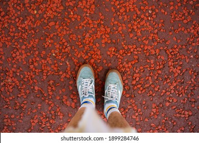 LONDON, UK - MAY 10, 2020: Top-down view of a man wearing a pair of Vans shoes and Dickies socks on the red road of The Mall, London.