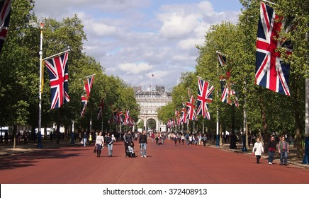 London, UK - May 11, 2015: Tourists walk along Pall Mall towards Buckingham Palace on a warm Spring day in London.