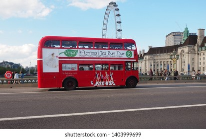 London, UK: May 13, 2019 in London, Traditional Pullman on bridge near London eye the tallest Ferris wheel in Europe at 135 meters -