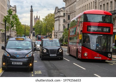 London, UK - May 13th 2021: London taxis, also known as black cabs, and a red London bus, pictured with the Duke of York column and the Houses of Parliament in the background in London.