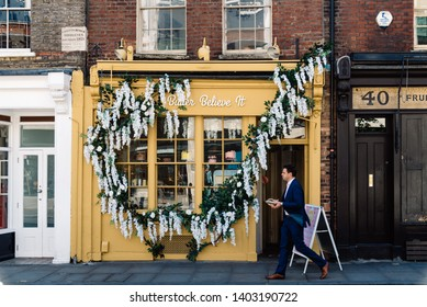 London, UK - May 14, 2019: Business man walking by storefront of hipster pastry shop in Shoreditch near the City of London