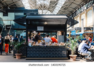 London, UK - May 14, 2019:  Old Spitalfields market with unidentified people. Bakery and pastry stall. The market  hosts arts and craft and street food market.