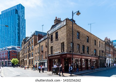 London, UK - May 14, 2019:  Old English restaurant in front of Spitalfields Market against skyscraper of the City of London