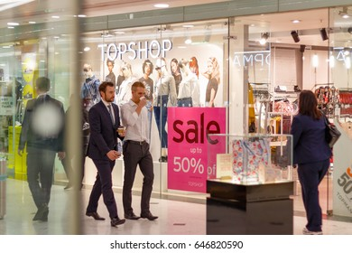 London, UK - May 15, 2017 - Topshop display window in Canary Wharf with a on sale sign while office workers walking in front of the store