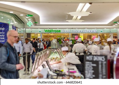 London, UK - May 15, 2017 - Waitrose Food, Fashion & Home, a chain of British supermarkets, in Canary Wharf with a busy crowd and food bars in the foreground