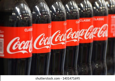 London, UK. May 18 2019. Large family size classic cola bottles in a row on a store shelf in the UK