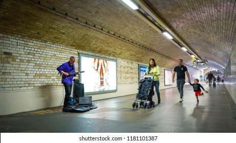 London, UK - May 20 2018: Unidentified street musician performs in a subway tunnel at South Kensington Station