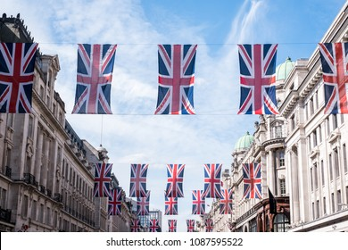 London UK, May 2018. Close up of buildings on Regent Street, iconic shopping street owned by The Crown Estate with row of British flags to celebrate the Royal Wedding of Prince Harry to Meghan Markle.