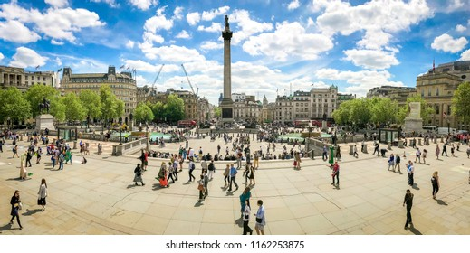 London, UK - May 2018: A crowd of people walking around Trafalgar Square on a sunny spring afternoon