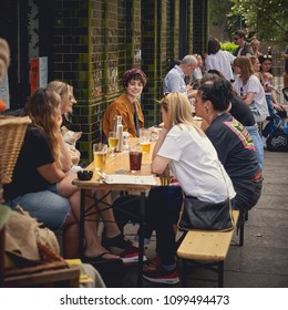London, UK - May, 2018. A group of young people having drinks outside a pub near Columbia Road in Shoreditch.