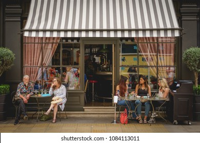 London, UK - May, 2018. Young people having drinks outside a bar coffee shop in Soho, central London.