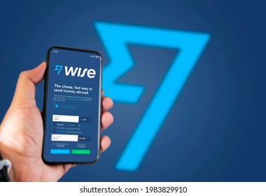 London, UK, May 2021: A hand holding a phone with the Wise app on the screen. Wise is a financial technology company services based in London, UK
