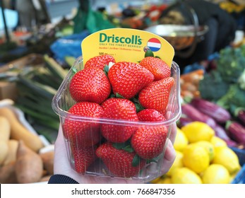 LONDON, UK - May 21, 2016: a hand holding Driscoll's strawberries in plastic package with vegetable stall in the background