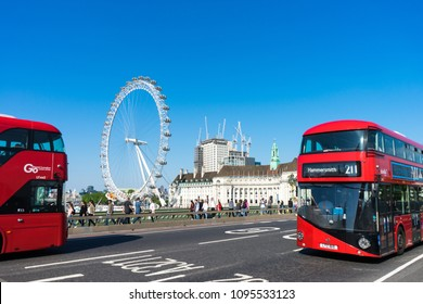 London, UK - May, 21st 2018: Red bus crosses Westminster Bridge, the London Eye in the background. Tourists cross the bridge. The sky is blue.