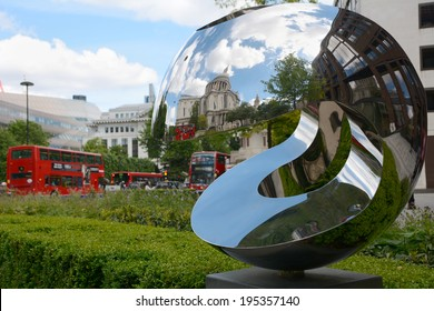 London, UK - May 25, 2014: St. Paul's Cathedral is reflected in a sculpture on May 25, 2014. Red London buses queue down Carter Lane beyond.