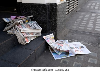 London, UK - May 25, 2014: Tabloid newspapers in a shop doorway on May 25, 2014. Headlines in the Daily Mirror report on the four sailors lost at sea when their yacht ran into trouble in the Atlantic.
