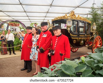 LONDON, UK - MAY 25, 2017: RHS Chelsea Flower Show 2017. Chelsea Pensioners pose with a young woman visitor near the Australian State Coach in the Great Pavilion.