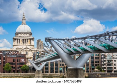 LONDON, UK MAY 26TH 2019 - View of St. Paul's Cathedral and the Millennium Bridge, taken from the south side of the Thames River embankment on a sunny day with puffy clouds.