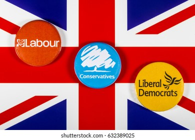 LONDON, UK - MAY 2ND 2017: Labour, Conservatives and Liberal Democrat pin badges over the UK flag, symbolizing the political battle for the General Election, on 2nd May 2017.