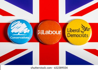 LONDON, UK - MAY 2ND 2017: Conservatives, Labour and Liberal Democrat pin badges over the UK flag, symbolizing the political battle for the General Election, on 2nd May 2017.