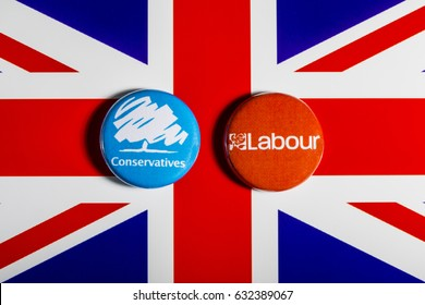 LONDON, UK - MAY 2ND 2017: Conservative and Labour Party pin badges over the UK flag, symbolizing the political battle for the General Election, on 2nd May 2017.