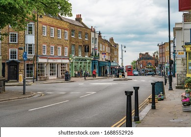 LONDON, UK - May 30, 2019 - A view down characterful Highgate High Street in Highgate, London. Victorian and Georgian shop fronts line the street and a red London bus is visible in the distance.